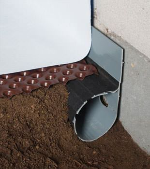 Closeup of a crawl space drainage system installed in Ithaca