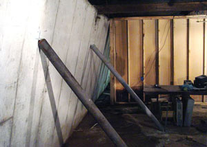 A severely tilting foundation wall propped up by steel beams in Cheboygan.